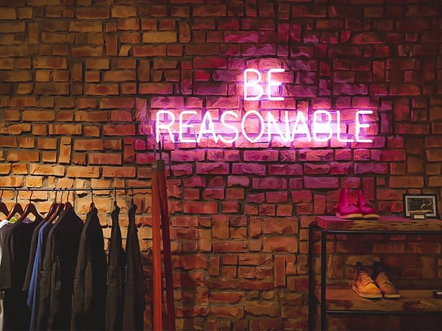Neon sign saying be reasonable
